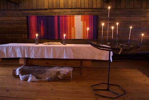 Pöydällä on valkoinen liina ja kynttilöitä.