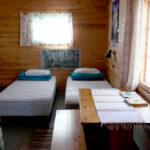 Huoneessa on kaksi sänkyä, pöytä, penkki ja petivaatteet.