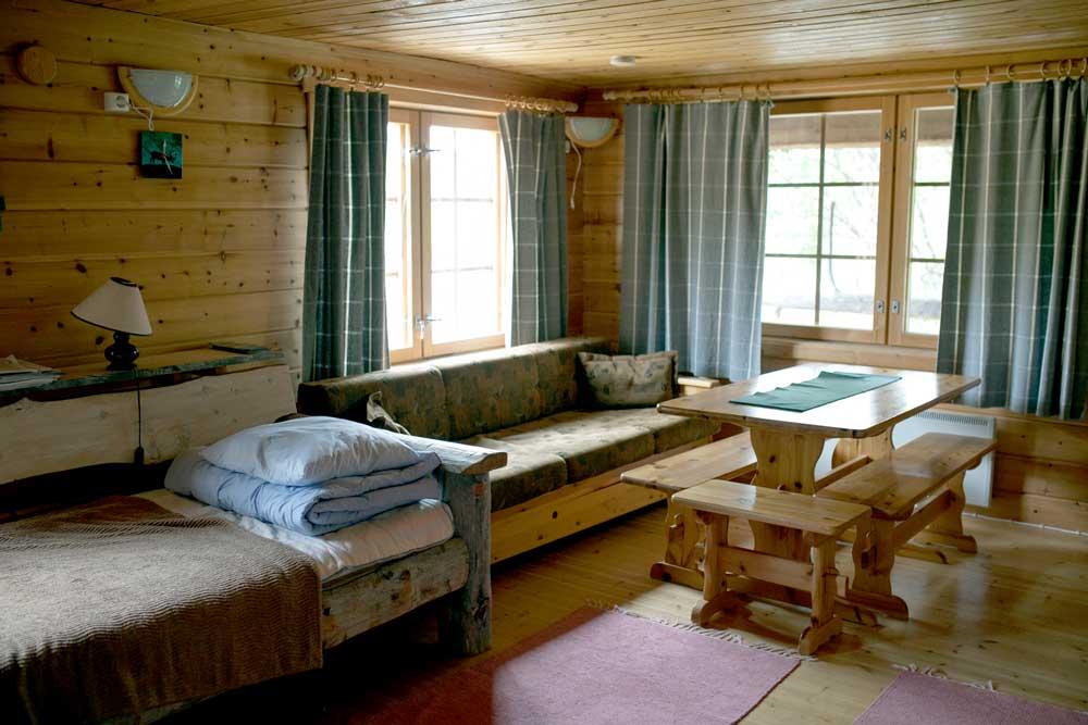 Huoneessa on sänky, sohva, pöytä ja penkki.