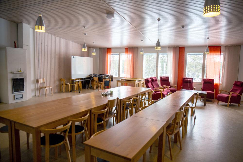 Isossa tilassa on kaksi pitkää pöytää, takka, piirtotaulu.