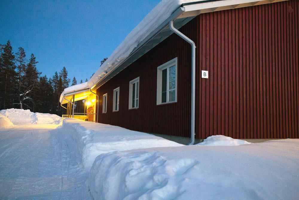 Punainen puutalo keskellä talvista maisemaa.