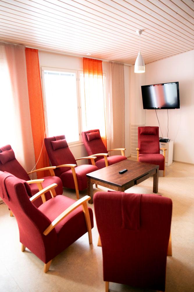 Huoneessa on kuusi nojatuolia. Seinällä on televisio.