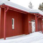 Punainen mökki talvisessa maisemassa.