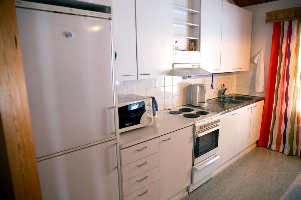 Keittiössä on jääkaappi, mikro, kavinkeitin, liesi ja tiskiallas.
