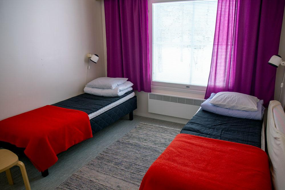 Huoneessa on kaksi yhden hengen sänkyä. Sänkyjen päällä on tyynyt, peitot ja punaiset torkkupeitot.