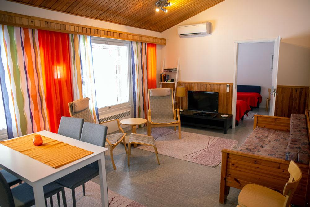 Huoneessa on sohva, televisio, pöytä tuoleineen ja kaksi lepotuolia.