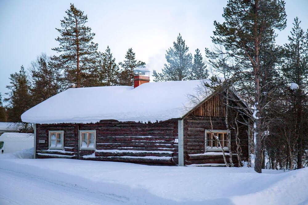 Hirsimökki keskellä talvista maisemaa.