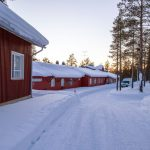 Punainen yksikerroksinen rakennus keskellä talvista maisemaa.