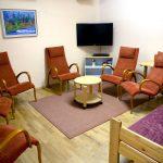 Oleskelutilassa on kuusi punaista nojatuolia. Seinän vieressä on lehtihylly. Seinällä on televisio.