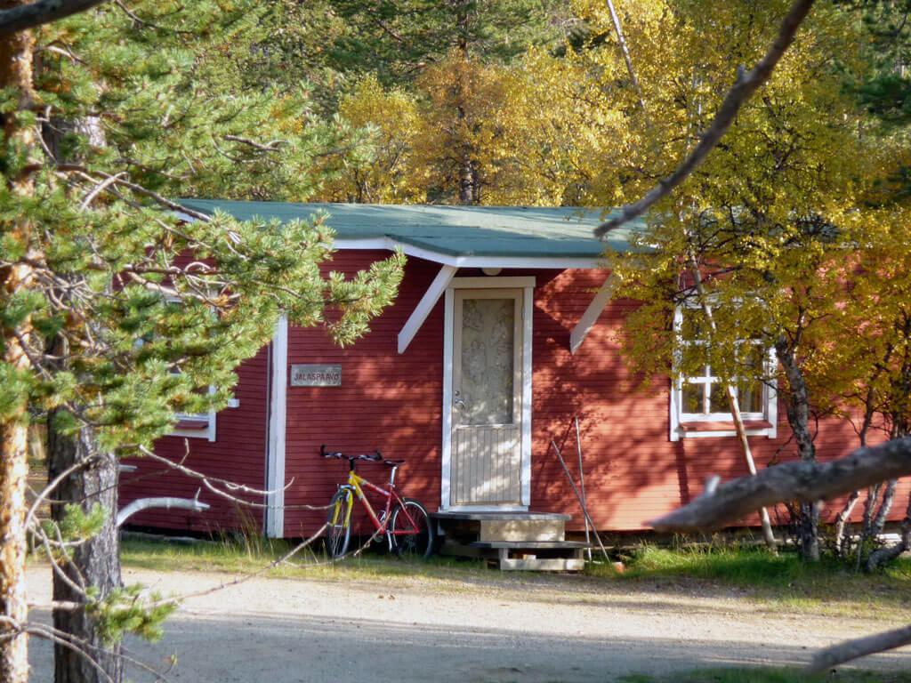 Punainen mökki puiden seassa. Oven vieressä on polkupyörä.