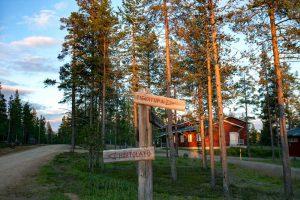 Kesäinen metsämaisema. Edessä on puuviitat, joissa lukee tievatupa ja hiihtolatu.